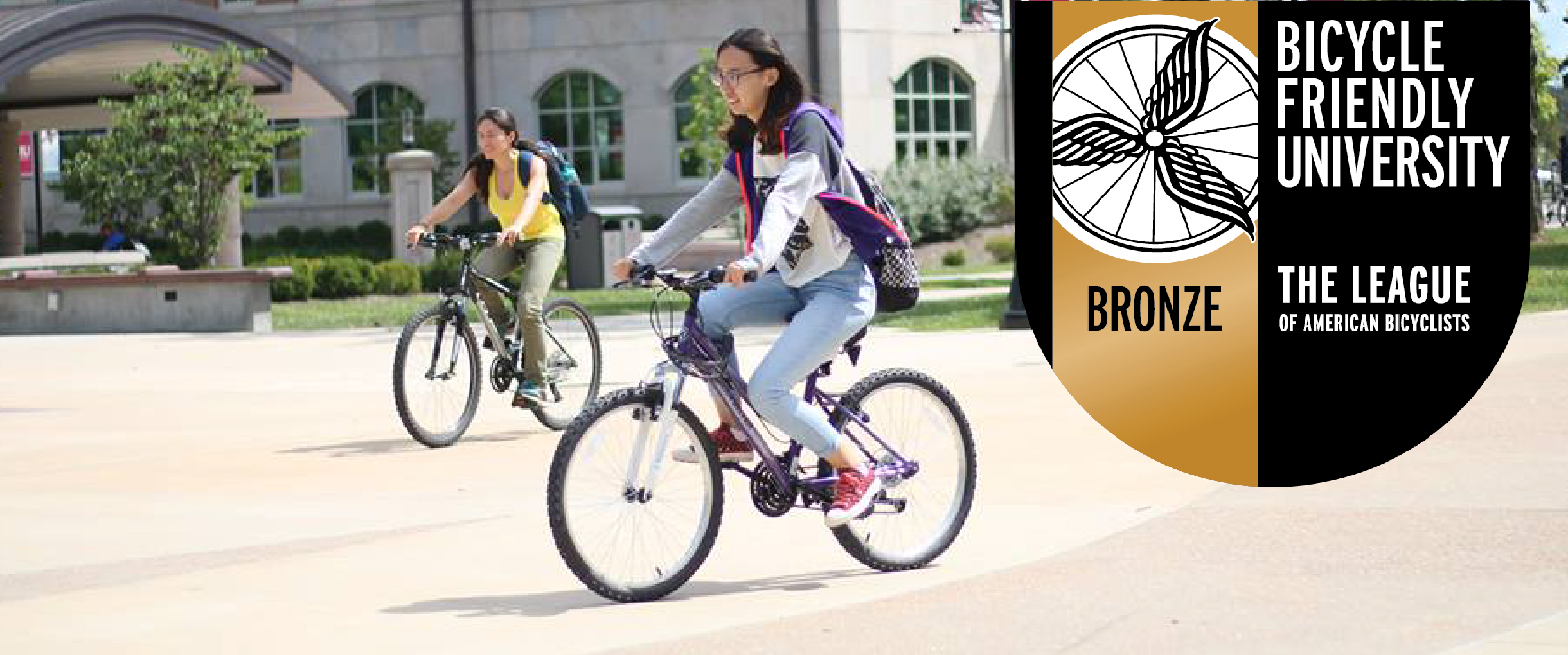 a bicyclist enjoys campus, bicycle friendly university symbol included